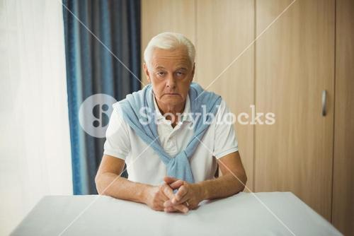 Sad senior man sitting at table