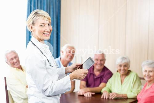 Smiling seniors and nurse holding a tablet