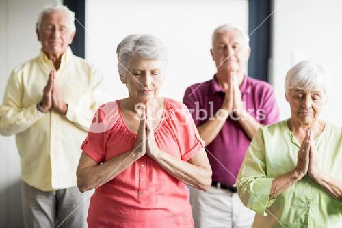 Seniors doing yoga with closed eyes