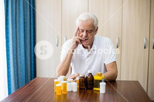 Senior sitting in front of medicine