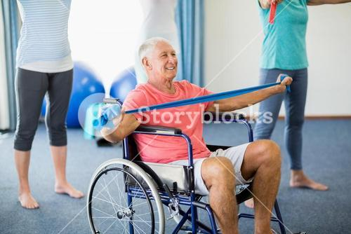 Senior in wheelchair exercising with exercising band