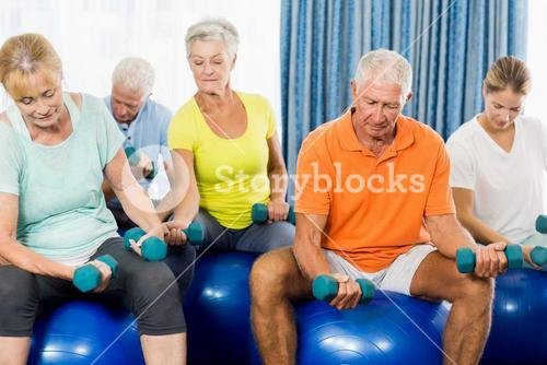 Seniors using exercise ball and weights