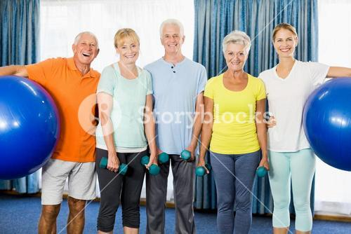 Seniors holding exercise ball and weights