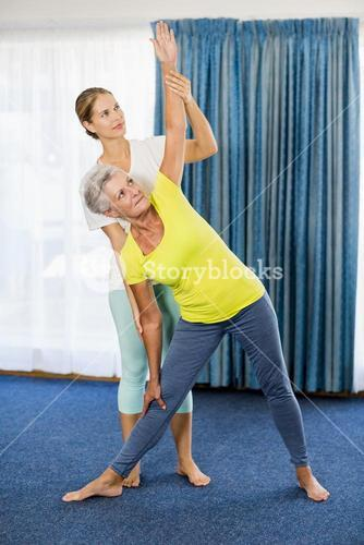Instructor helping senior woman with sport exercises
