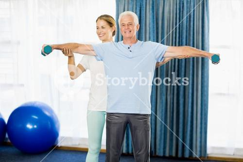 Instructor helping senior man with weights