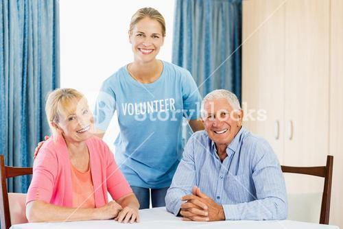 Volunteer taking care of senior couple