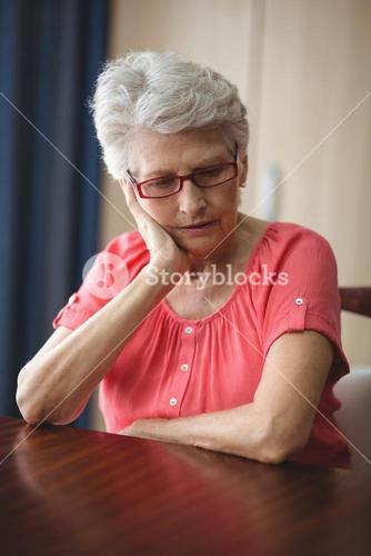 Sad senior woman sitting at a table