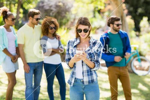Woman using mobile phone with friends in background