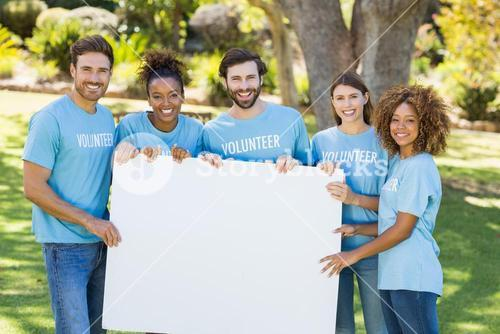 Portrait of volunteer group holding blank sheet