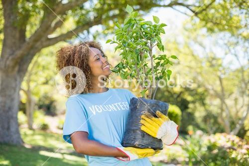 A volunteer woman holding plant