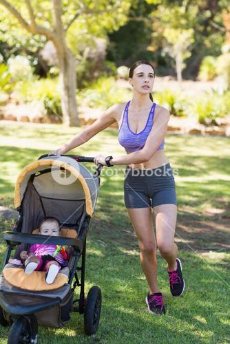 Young woman walking with baby stroller