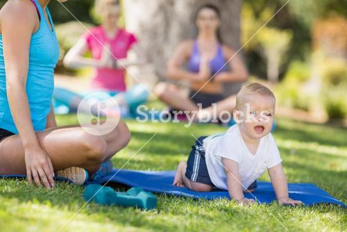 Woman exercising and her baby crawling