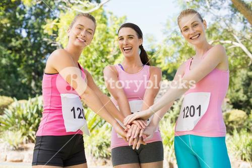 Young athlete women forming hands stack