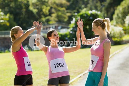 Female athletes giving high five to each other