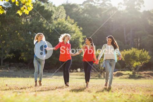 Beautiful women holding hands and walking together in park