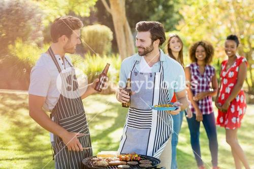 Men holding a beer bottle while preparing barbecue grill
