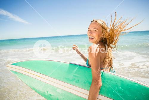 Woman running with surfboard on beach