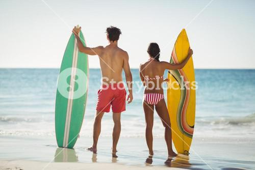 Couple standing with surfboard on beach