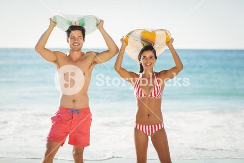 Couple posing with surfboard on beach