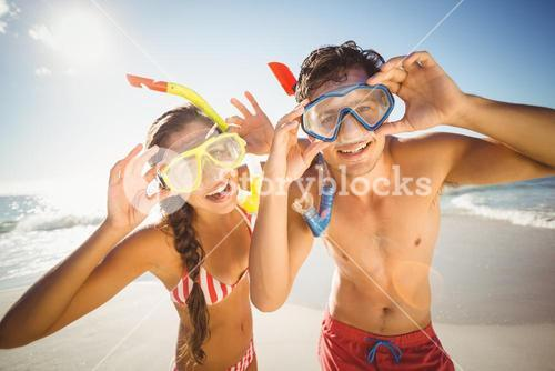 Couple posing with diving mask on beach