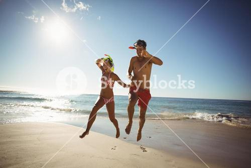 Couple wearing diving mask jumping on beach