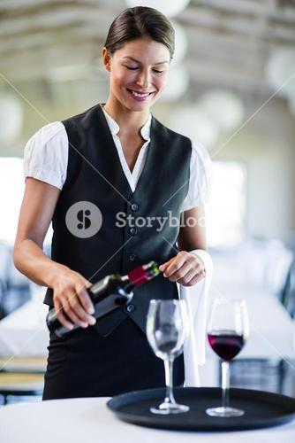 Smiling waitress pouring red wine in a glass