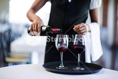 Mid section of waitress pouring red wine in a glass