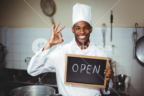 Smiling chef showing chalkboard with open sign