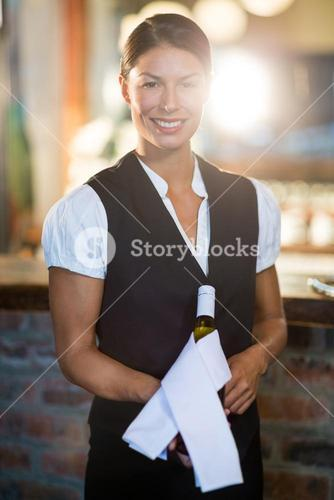 Waitress holding champagne bottle wrapped in napkin