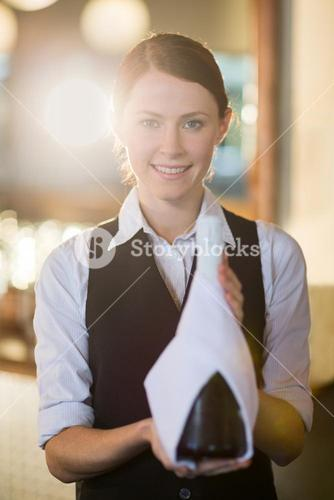 Waitress holding champagne bottle wrapped in towel