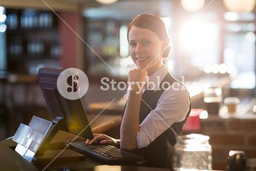 Portrait of waitress using a computer at counter