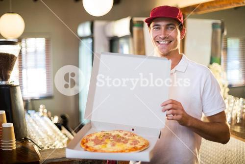 Pizza delivery man showing fresh pizza