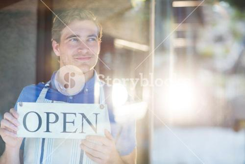Smiling chef holding open sign