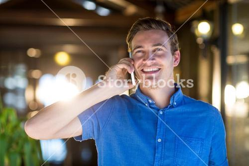 Happy man talking on mobile phone