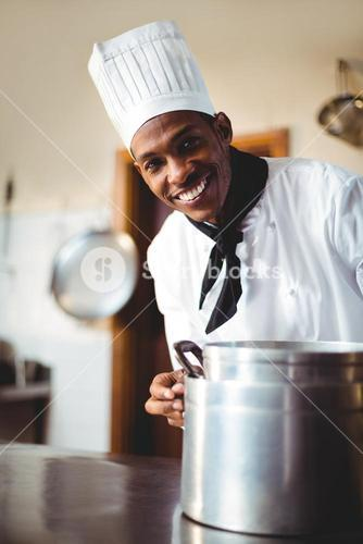 Smiling chef in kitchen holding cooking pot