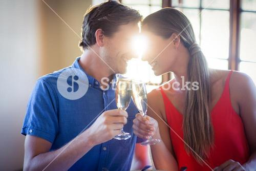 Young couple looking face to face and toasting champagne flutes