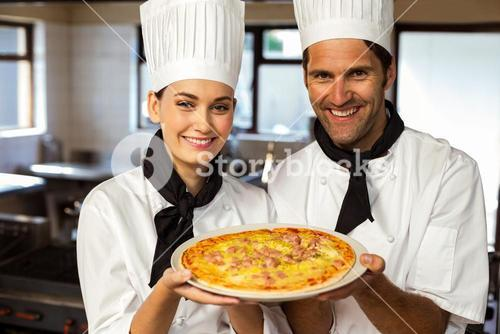 Portrait of two chef presenting a pizza