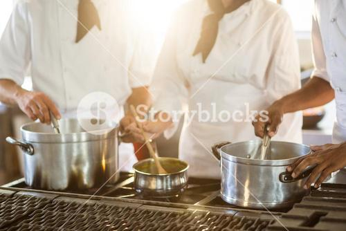 Mid section of chefs stirring in pot
