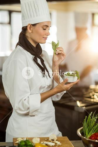 Young female chef smelling herb