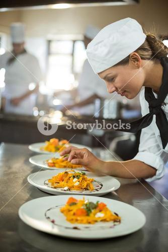 Female chef garnishing plate of food