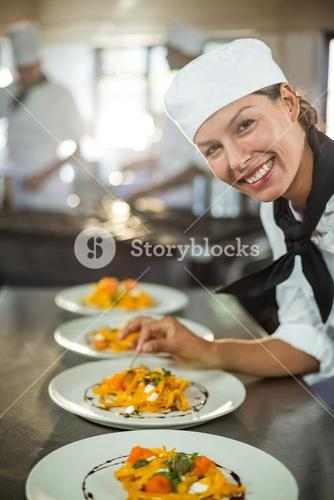 Portrait of female chef garnishing plate of food
