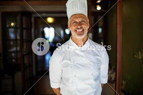 Portrait of chef standing with hands behind back
