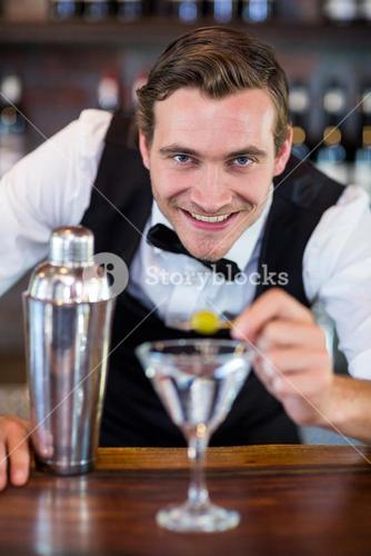Portrait of bartender garnishing cocktail with olive