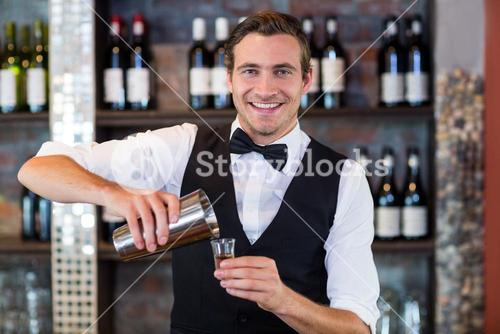 Portrait of bartender pouring tequila into shot glass