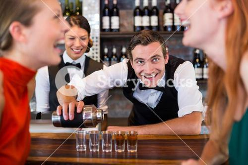 Bartender pouring tequila into shot glasses
