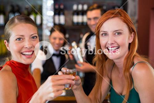 Portrait of happy friends holding a tequila shot in front of bar counter