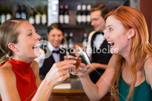 Happy friends holding a tequila shot in front of bar counter