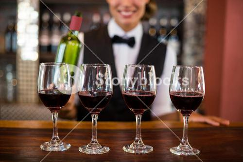 Four glasses of red wine ready to serve on bar counter
