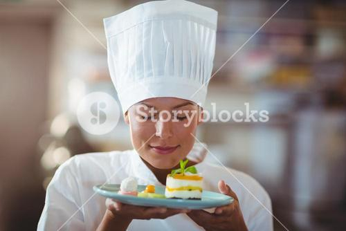 Female chef with eyes closed smelling food