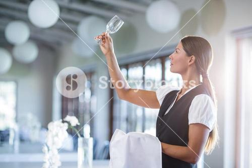 Smiling waitress holding up a empty wine glass